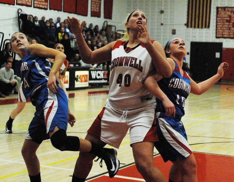 Catherine Avalone/The Middletown Press Cromwell's Lindsay Langenauer battles Coginchaug's Liv Corazzini (15) and Jessica Solomon (34) in the paint Friday night in Cromwell. Cromwell defeated Coginchaug 45-30.