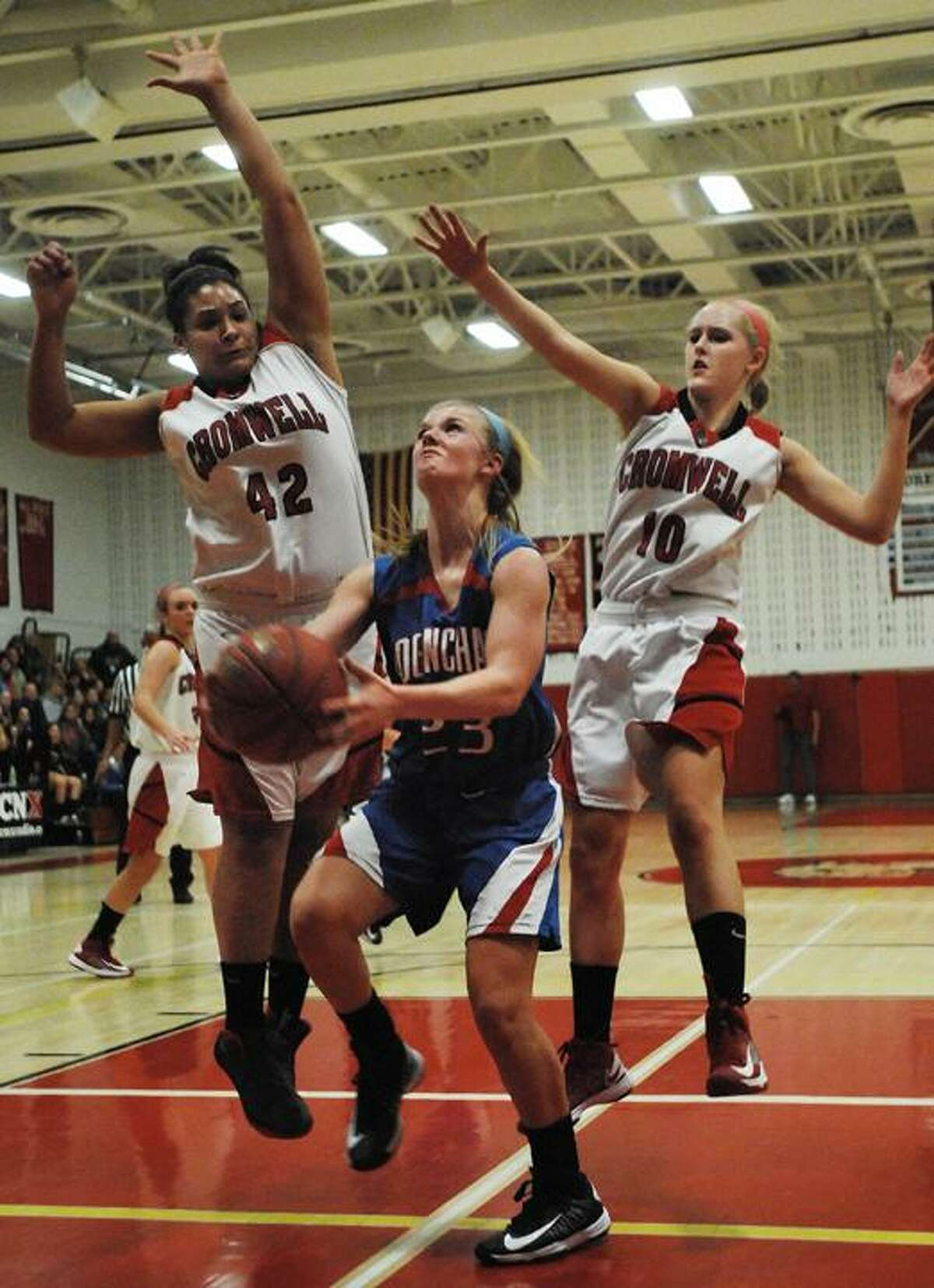 Catherine Avalone/The Middletown Press Cromwell's Mya Villard (42) and Emily Appleby (10) defend Coginchaug's Kim Romanoff as she drives in the paint Friday night in Cromwell. Cromwell defeated Coginchaug 45-30.