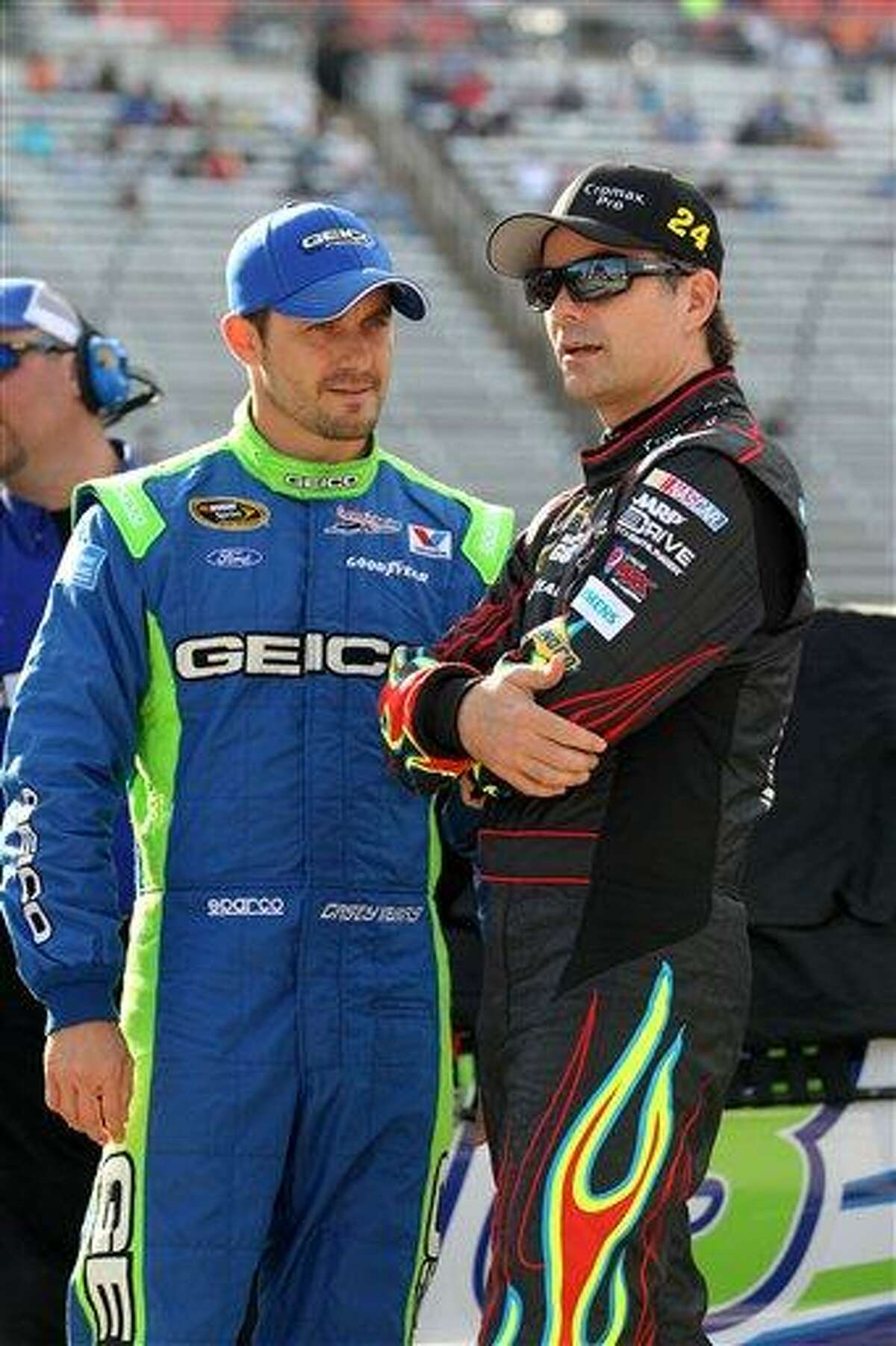 Casey Mears, left, and Jeff Gordon, right, talk as they stand by their cars on pit road during qualifying for the NASCAR Sprint Cup Series NRA 500 auto race at Texas Motor Speedway, Friday April 12, 2013, in Fort Worth, Texas. (AP Photo/Tim Sharp)