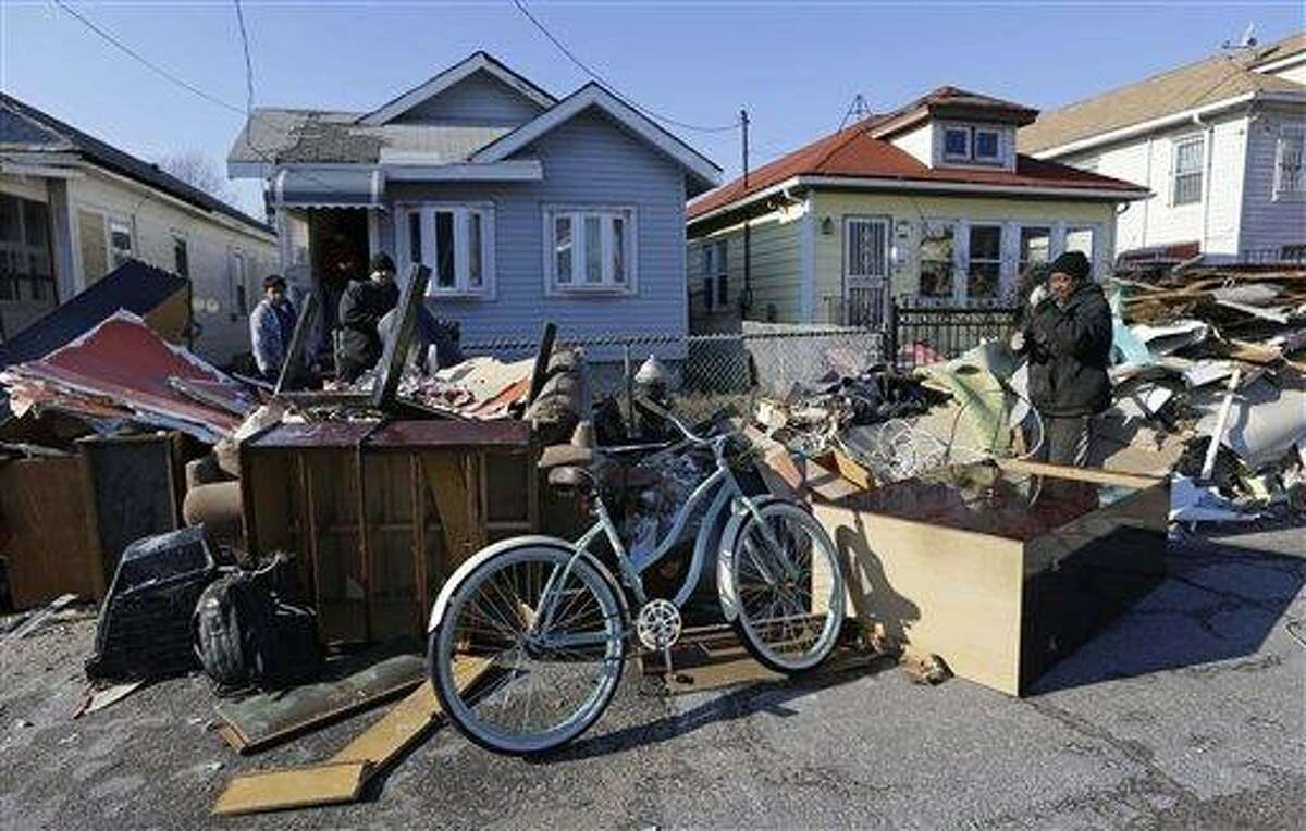 Metal collector Shaun Johnson, far right, salvages wiring and cable from a pile of storm-damaged, discarded personal belongings left on the street in the Rockaways section of New York on Christmas Day, Tuesday, Dec. 25, 2012. Johnson says,