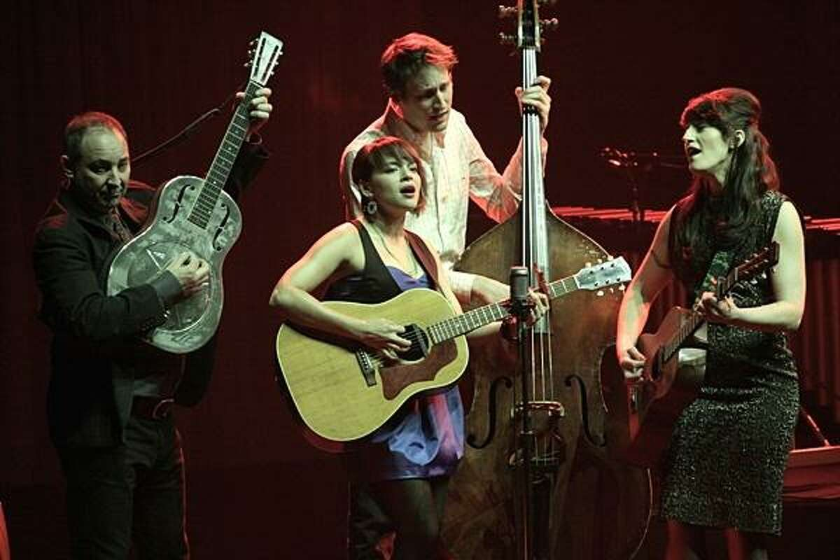 """Norah Jones and her band are shown performing together on stage during a """"live"""" concert."""