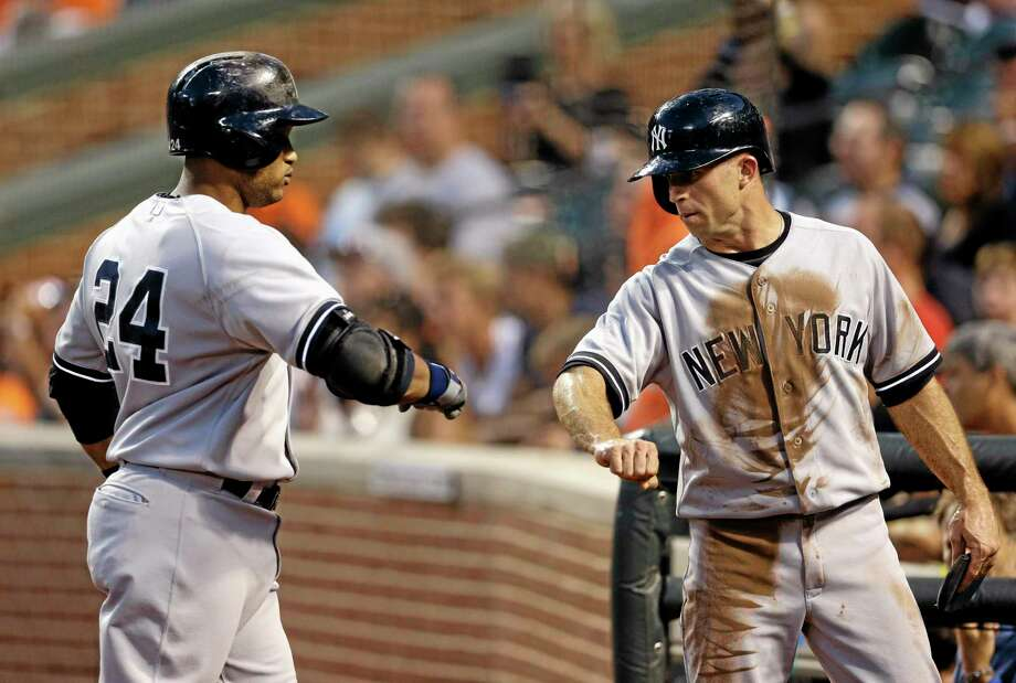 The Yankees' Brett Gardner, right, fist-bumps teammate Robinson Cano after he scored a run against the Baltimore Orioles on Cano's groundout Wednesday in Baltimore. Photo: Patrick Semansky — The Associated Press  / AP