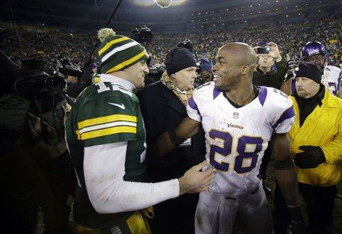 Green Bay Packers quarterback Aaron Rodgers (12) and Minnesota Vikings running back Adrian Peterson (28) talk after an NFL wild card playoff football game Saturday, Jan. 5, 2013, in Green Bay, Wis. Packers won 24-10. (AP Photo/Jeffrey Phelps)