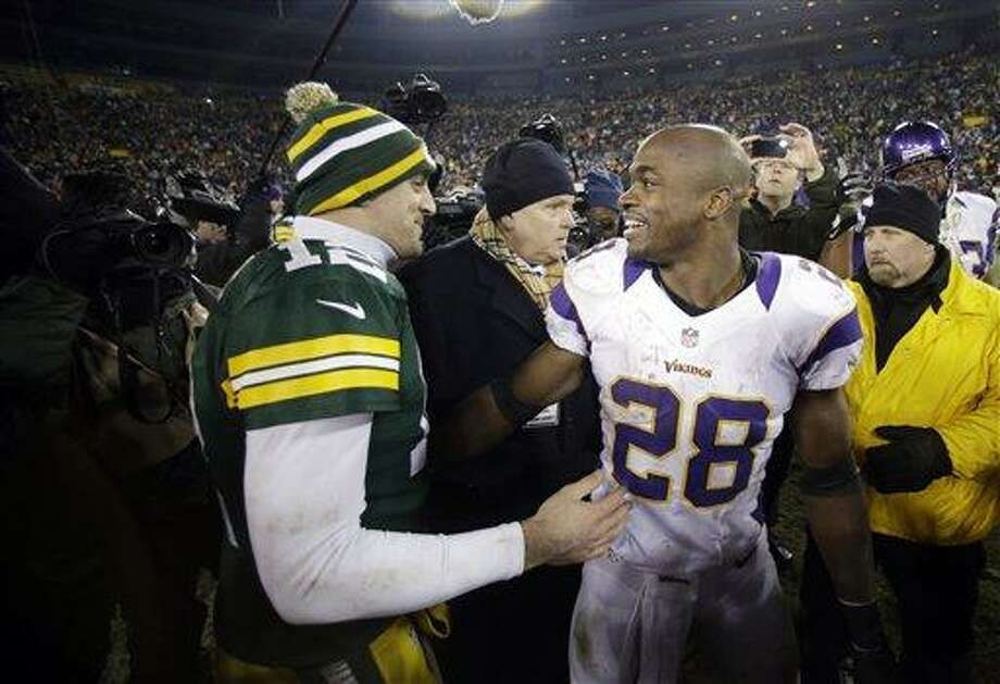 Green Bay Packers quarterback Aaron Rodgers (12) and Minnesota Vikings running back Adrian Peterson (28) talk after an NFL wild card playoff football game Saturday, Jan. 5, 2013, in Green Bay, Wis. Packers won 24-10. (AP Photo/Jeffrey Phelps) Photo: ASSOCIATED PRESS / AP2013