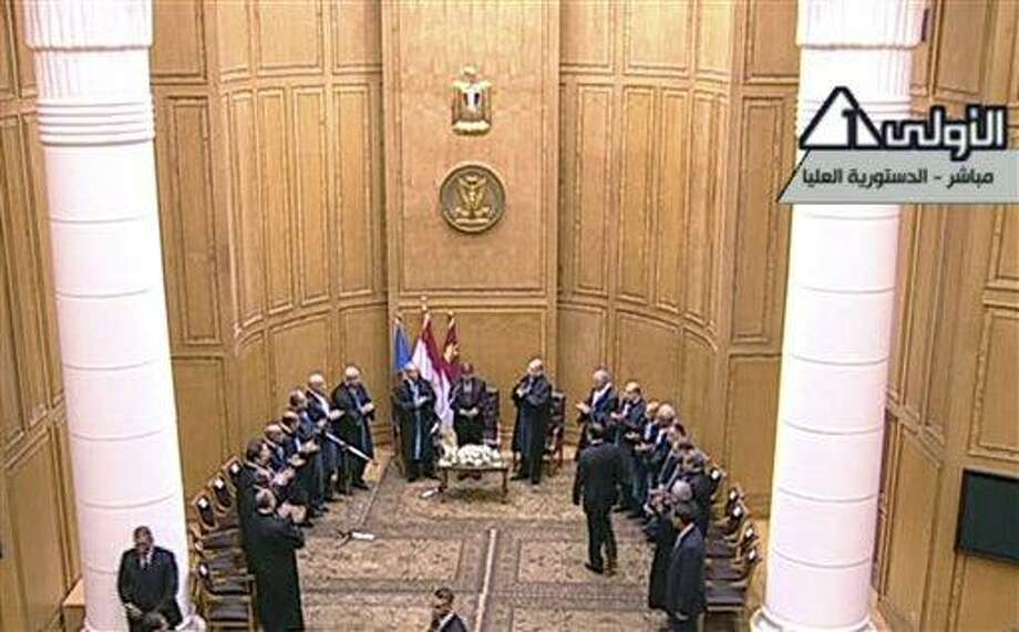 In this image made from Egyptian State Television, judges from Egypt's Supreme constitutional court applaud Mohammed Morsi, center, after he was sworn in as President in Cairo, Egypt, Saturday, June 30, 2012. Islamist Mohammed Morsi has been sworn in before Egypt's highest court as the country's first freely elected president, succeeding Hosni Mubarak who was ousted 16 months ago.(AP Photo/Egyptian State TV) Photo: ASSOCIATED PRESS / AP2012