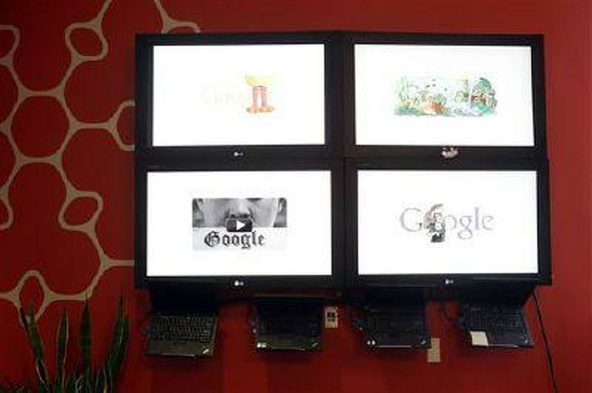 Computer screens flash the Google home page at Google headquarters in Mountain View, Calif., Thursday, April 25, 2013.