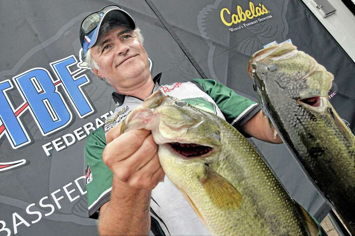 Newington angler Dino Moutogiannis, formerly of Middletown, holds two of the five large mouth bass Friday afternoon shortly before winning the The Bass Federation Eastern Division Championship at Harbor Park in Middletown. Moutogiannis has been fishing the Connecticut River for 25 years. Moutogiannis reeled in 15 fish during the three-day competition weighing 30 pounds and 8 ounces. Moutogiannis, a member of the Connecticut State Team of The Bass Federation and his teammates caught 196 pounds 10 ounces and 117 fish in total to clinch first place. Catherine Avalone — The Middletown Press