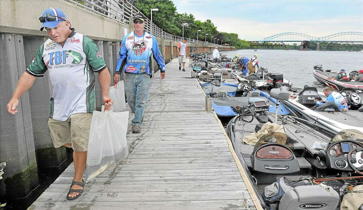 Westbrook angler Ken Bugden, left, and John Ahern, of Ashaway, R.I., carry their day's catch to the running bump station at Harbor Park to get counted and weighed Friday afternoon. Bugden, a member of the Connecticut State Team, placed 16th overall and Ahern came in 20th in The Bass Federation Eastern Division Championship on the Connecticut River in Middletown. Catherine Avalone — The Middletown Press
