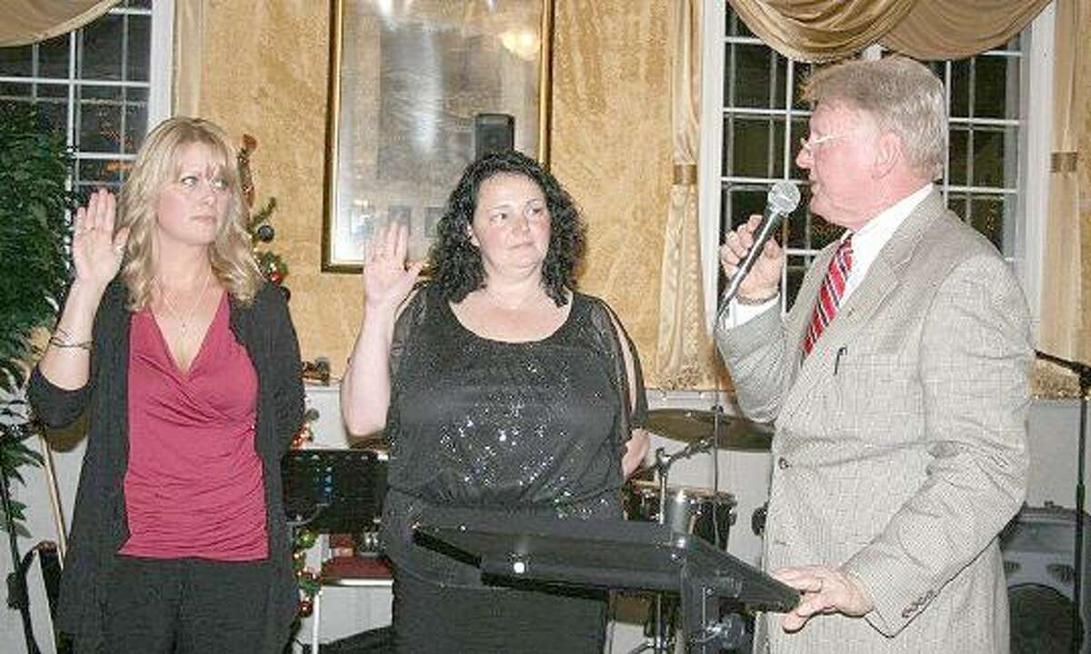 Photo courtesy of Tom and Anne Sweeney Jen Day, left, and Mimi Perrotti, center, are sworn in as the newest members of East Hampton Rotary by past president Red McKinney. Day, whose grandfather was a founding member of the group, is the owner of Confidentially Yours, a medical prosthetics company, while Perrotti owns Mimi Design Lakeside Signs, a graphic design company.