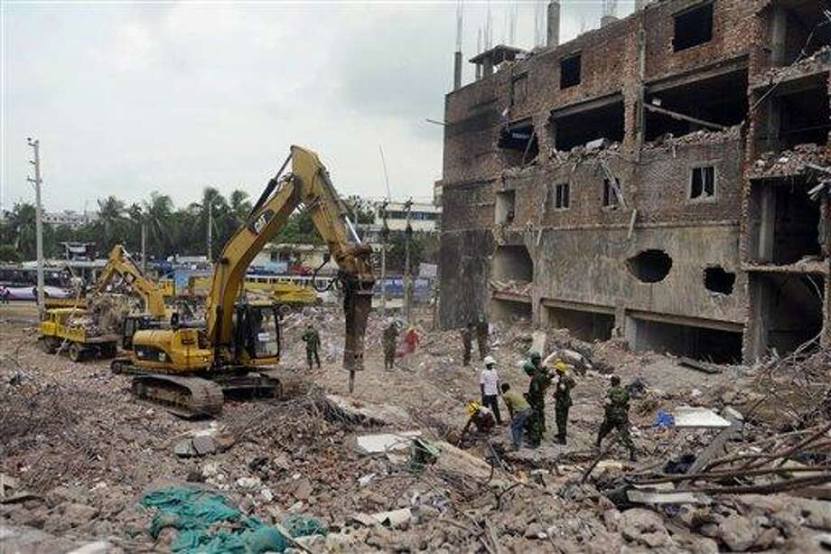 Bangladeshi workers and army personnel work to clean the debris and fallen ceiling of the garment factory building which collapsed in Savar near Dhaka, Bangladesh, Friday, May 10, 2013. The death toll from a garment factory building that collapsed more than two weeks ago near the Bangladeshi capital soared past 1,000 on Friday, with no end in sight to the stream of bodies being pulled from the wreckage of the worst-ever garment industry disaster. (AP Photo/Ismail Ferdous) Photo: AP / AP