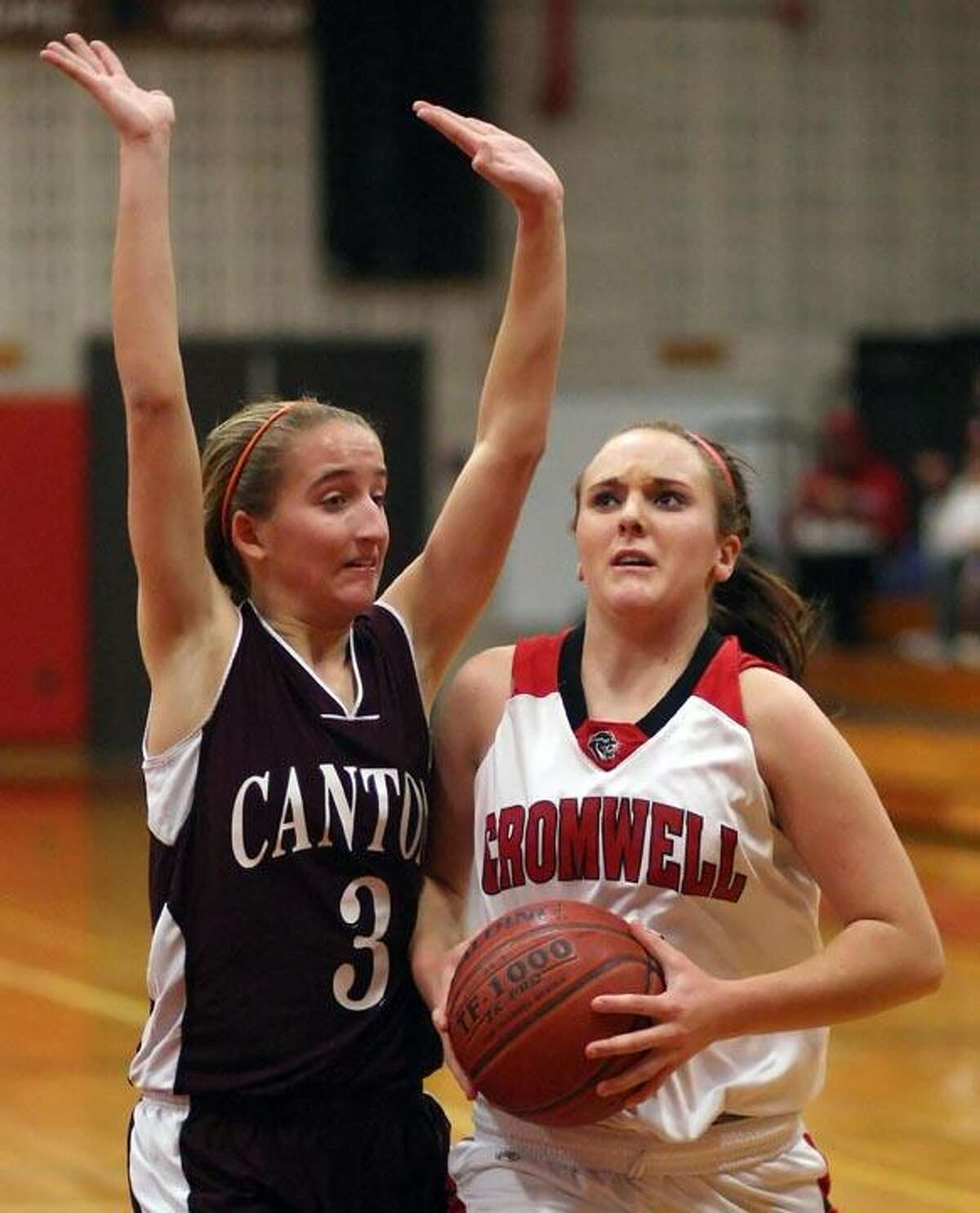 Special to the Press 12.30.11. Cromwell's Alexa Riley drives the baseline past Canton's Amanda Curvino in Friday's basketball game. Cromwell won, 67-23. To buy a glossy print of this photo and more, visit www.middletownpress.com