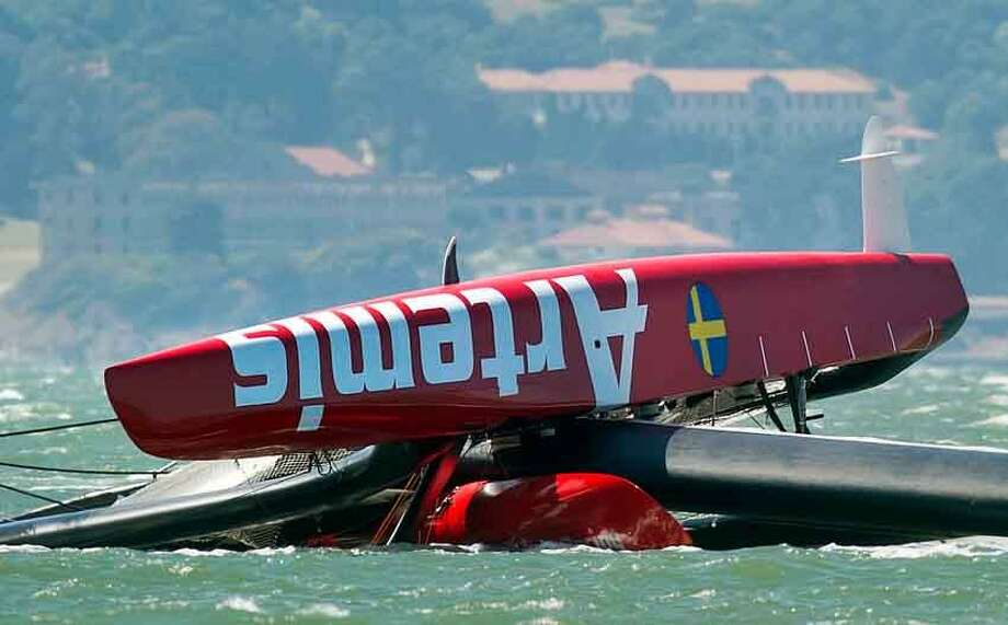 "The Artemis Racing AC72 catamaran, an America's Cup entry from Sweden, lies capsized after flipping over during training in San Francisco Bay on Thursday, May 9, 2013, in San Francisco. Artemis Racing said Andrew ""Bart"" Simpson, an Olympic gold medalist from Great Britain, died after the capsized boat's platform trapped him underwater for about 10 minutes. Behind are the historic buildings of the Angel Island internment camp. (AP Photo/Noah Berger) Photo: ASSOCIATED PRESS / AP2013"