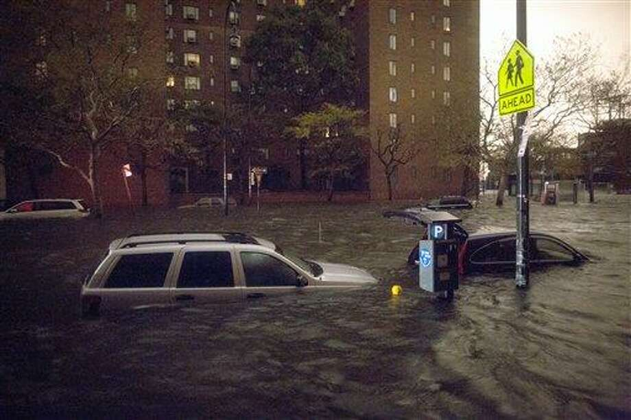 Vehicles are submerged on 14th Street near the Consolidated Edison power plant, Monday, Oct. 29, 2012, in New York. Sandy continued on its path Monday, as the storm forced the shutdown of mass transit, schools and financial markets, sending coastal residents fleeing, and threatening a dangerous mix of high winds and soaking rain. (AP Photo/ John Minchillo) Photo: AP / FR170537 AP