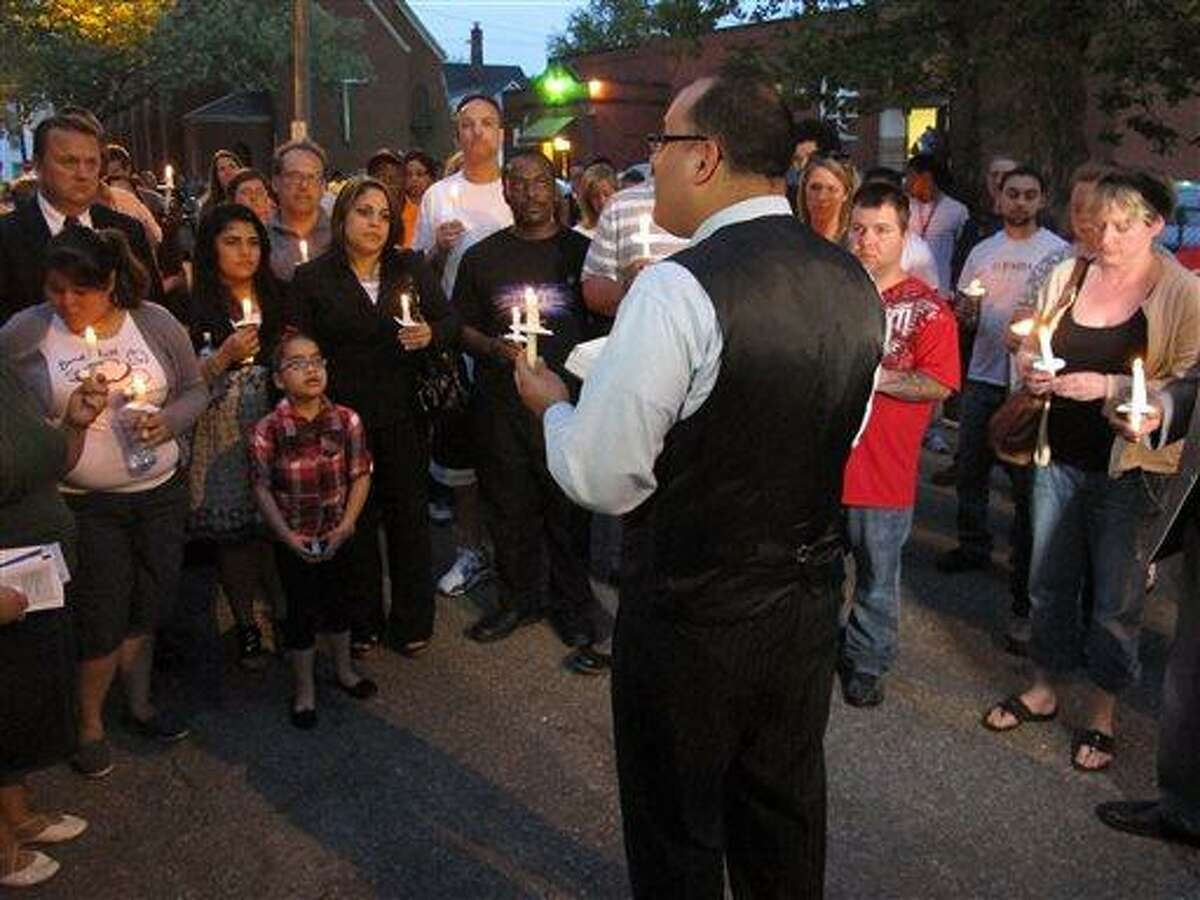 Pastor Omar Medina leads a candlelight prayer vigil on Thursday, May 9, 2013, in Cleveland, half a block from the house where investigators say three women were imprisoned by a man for nearly a decade. Medina told participants in the vigil that the message of the women's escape was never to lose hope. (AP Photo/Andrew Welsh-Huggins)