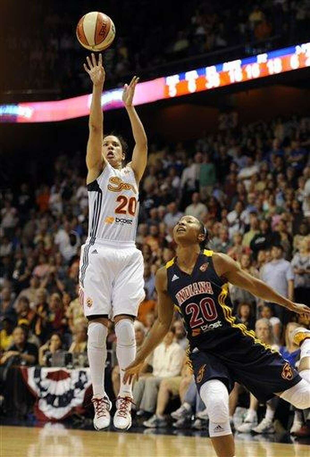 Connecticut Sun's Kara Lawson releases the game-winning shot while guarded by Indiana Fever's Briann January in overtime of a WNBA basketball game in Uncasville, Conn., Tuesday, June 19, 2012. Connecticut won 88-85. (AP Photo/Jessica Hill)