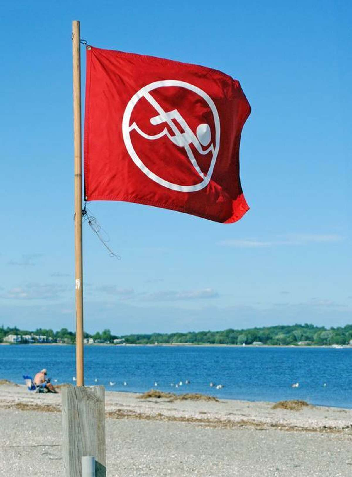 Silver Sands State Park beach in Milford has flags up saying it's not safe to swim because of an excessive amount of bacteria in the water. Photo by Jen Fengler for the Register