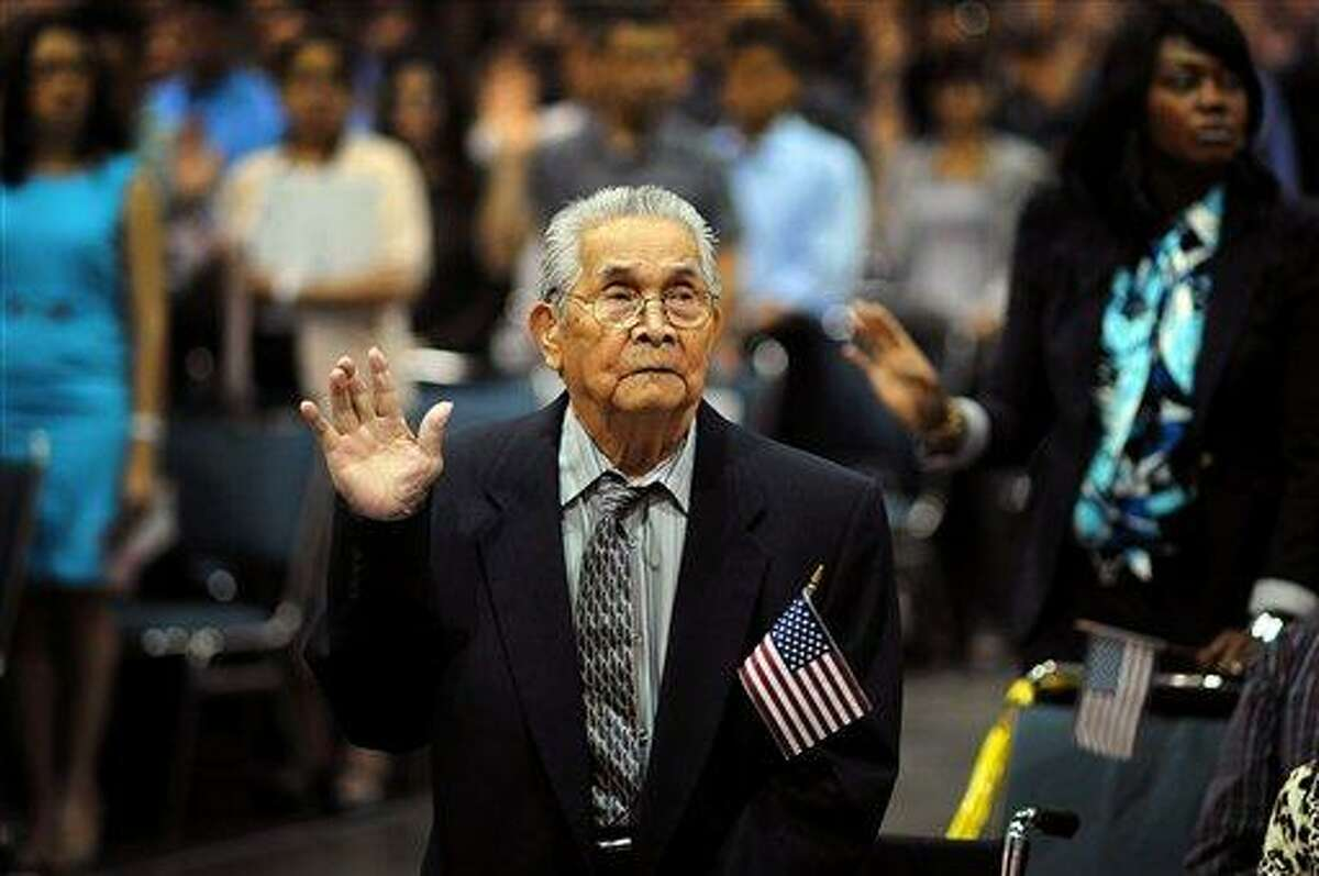 Joaquin Arciago Guzman, a 102-year-old military veteran participates in a naturalization ceremony Wednesday in California. He was one of more than 7,000 people to become naturalized citizens during ceremonies at the Los Angeles Convention Center. Associated Press