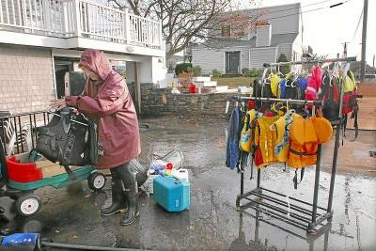 Catherine Avalone/The Middletown Press Sudbury, Massachusetts resident Deidra Vingers spent much of day Tuesday hanging life jackets out to dry after 34 inches of water accumulated in the basement of their Westbrook summer home following Hurricane Sandy.