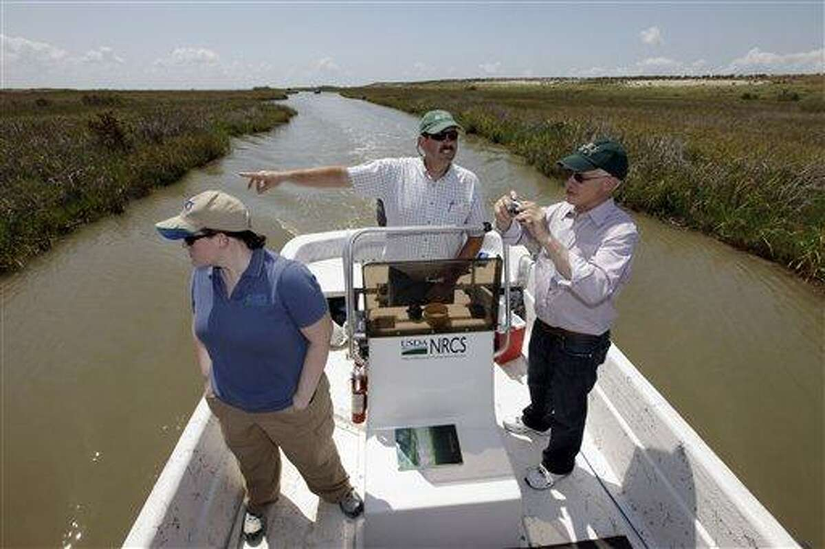 FILE - In this Tuesday, June 28, 2011 file photo, Scott Alford, center, a soil conservationist for the Natural Resources Conservation Service, points out features of a manmade marsh to Harris Sherman, right, undersecretary for natural resources and the environment at the U.S. Department of Agriculture and Julie Grogan-Brown, left, also with the USDA, near Baytown, Texas. The marsh is part of a project to restore lost wetlands and islands off the Texas coast. A report released to The Associated Press says the Natural Resources Conservation Service has already committed more than a half-billion dollars to the Gulf Coast in the past two years, nearly one-fifth of it on projects directly linked to recovery from the 2010 oil spill. (AP Photo/David J. Phillip, File)