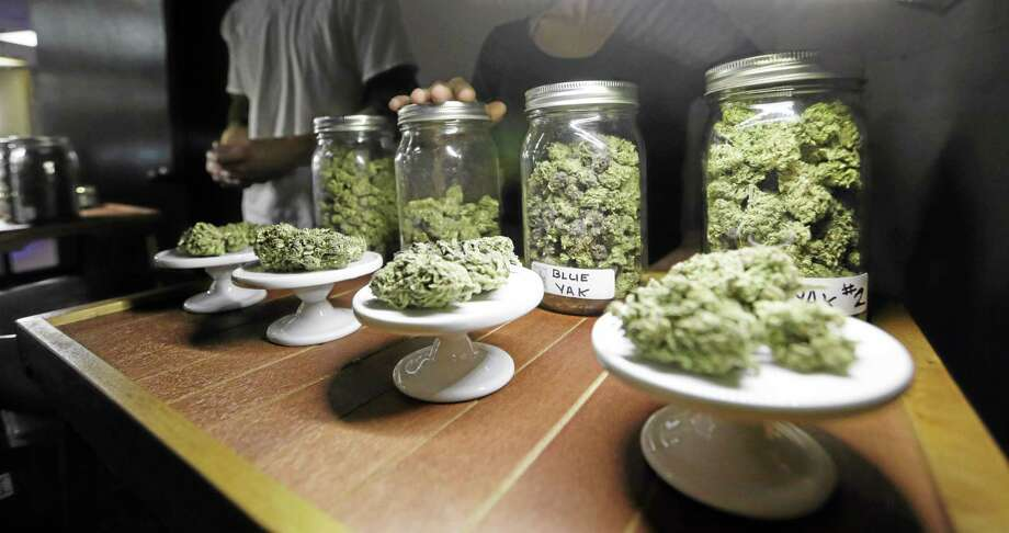 """FILE - This Feb. 13, 2013 shows different strains of marijuana are displayed during the grand opening of the Seattle location of the Northwest Cannabis Market, for sales of medical marijuana products.  It took 50 years for American attitudes about marijuana to zigzag from the paranoia of """"Reefer Madness"""" to the excesses of Woodstock back to the hard line of Just Say No. And now, in just a few short years, public opinion has shifted so dramatically toward pragmatic acceptance of marijuana that even those who champion legalization are surprised at how quickly attitudes are changing and states are moving to approve the drug for medical use and just for fun. (AP Photo/Elaine Thompson, File) Photo: AP / AP"""