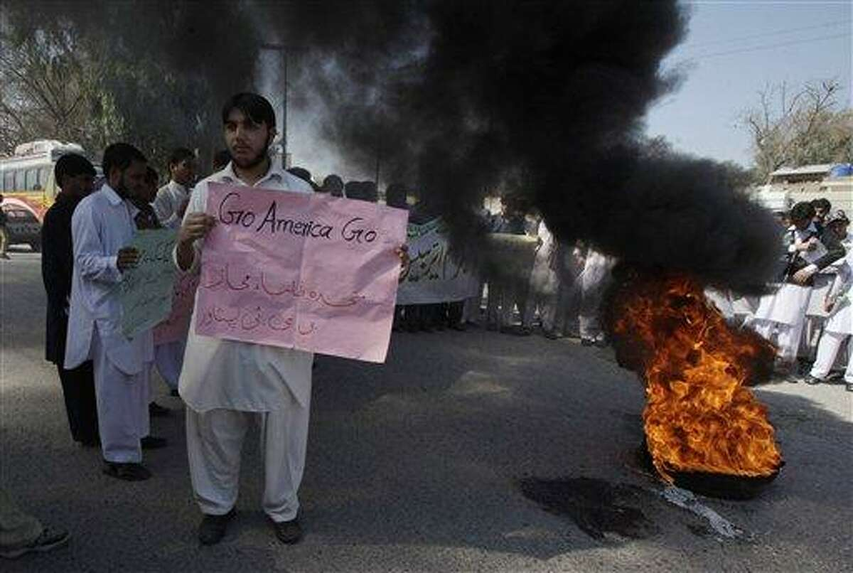 """Pakistani students condemn the reported burning of Qurans in Afghanistan by U.S. troops, in Peshawar, Pakistan, Wednesday. The Placard reads, """"United Students Front."""" Associated Press"""