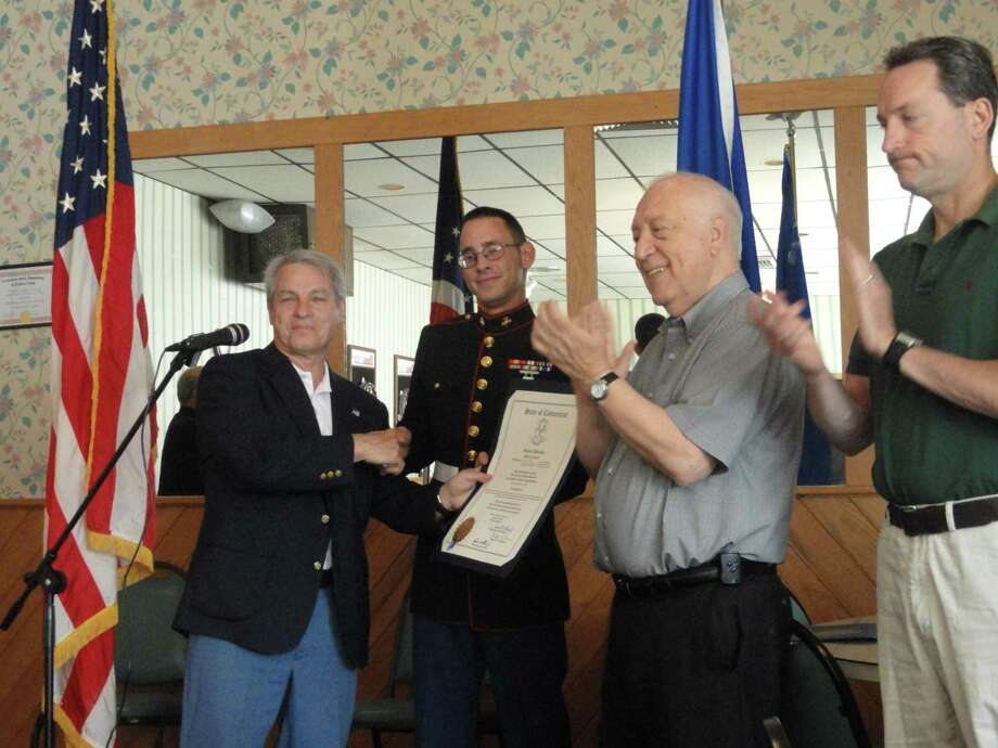 From left, state Sen. Len Suzio shakes the hand of Middletown native Marine Lance Cpl. Aaron J. Boyce, as state Rep. Joseph Serra and state Sen. Paul Doyle applaud. The June 23 ceremony, held at American Legion Post 75, was dedicated to welcoming homeBoyce from his recent Afghanistan deployment and to honor him for his military service.