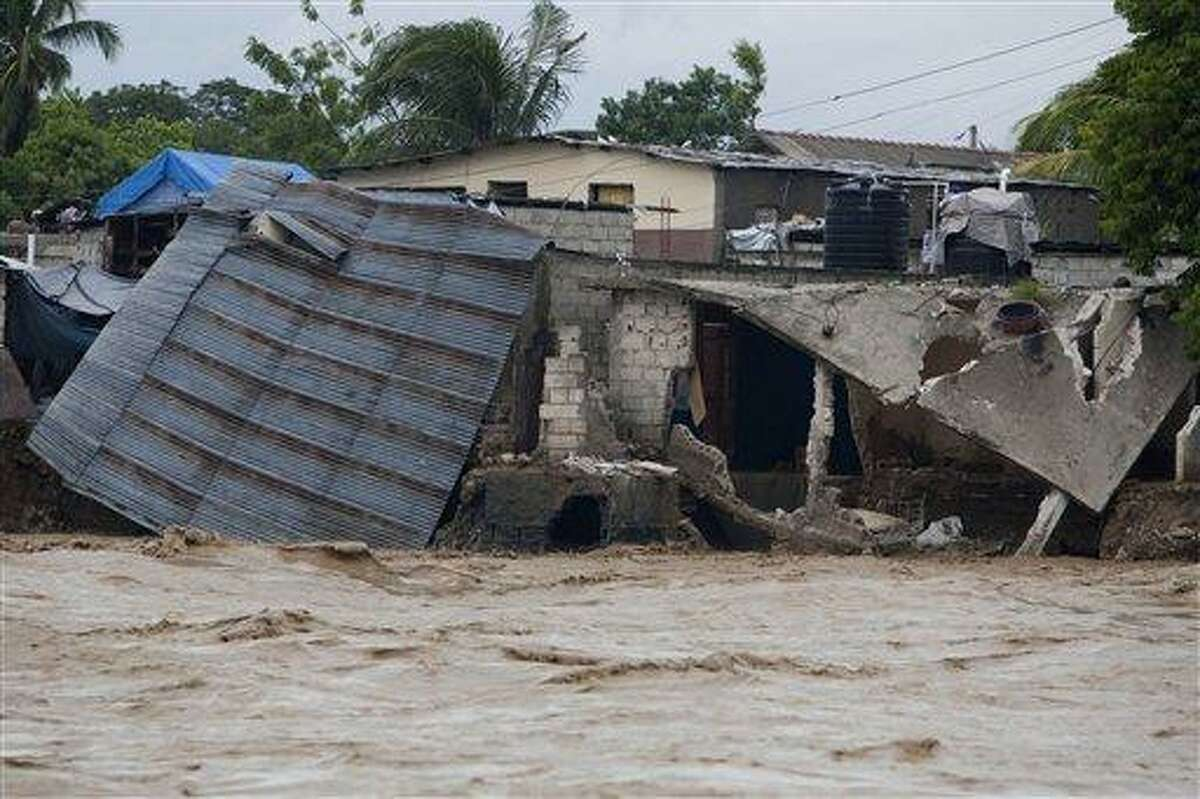 Damaged houses are seen on the shore of a river after heavy rains brought by Hurricane Sandy in Port-au-Prince, Haiti Oct. 25. Sandy was blamed for the death of an elderly man in Jamaica who was crushed by a boulder. Another man and two women died while trying to cross storm-swollen rivers in southwestern Haiti. AP Photo/Dieu Nalio Chery