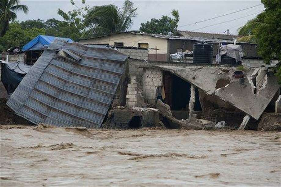 Damaged houses are seen on the shore of a river after heavy rains brought by Hurricane Sandy in Port-au-Prince, Haiti Oct. 25. Sandy was blamed for the death of an elderly man in Jamaica who was crushed by a boulder. Another man and two women died while trying to cross storm-swollen rivers in southwestern Haiti. AP Photo/Dieu Nalio Chery Photo: ASSOCIATED PRESS / AP2012