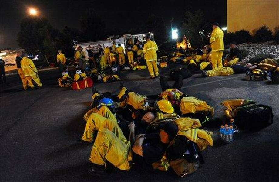 Colorado Springs, Colo., firefighters rest in the parking lot next to Station 9 on Garden of the Gods Road Tuesday between shifts fighting the Waldo Canyon Fire. Every firefighter available in the city was called in to fight the fire. Associated Press Photo: AP / the gazette