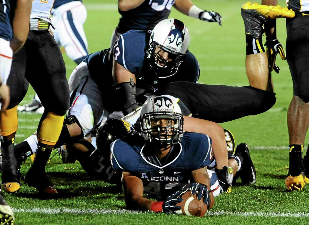 UConn running back Lyle McCombs, bottom, looks up to an official at the goal line during the first half of an NCAA college football game against Towson.