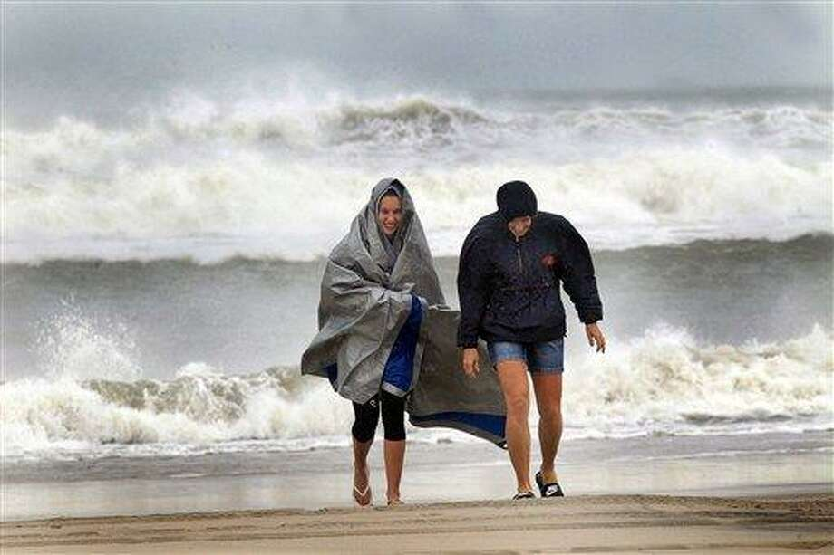 McKayla Walker and her mother, Holly, fight the wind and enjoy their first time to see hurricane waves on the Atlantic Ocean, Saturdayin Atlantic Beach, N.C.  AP Photo/The Jacksonville Daily News, Chuck Beckley Photo: AP / The Daily News