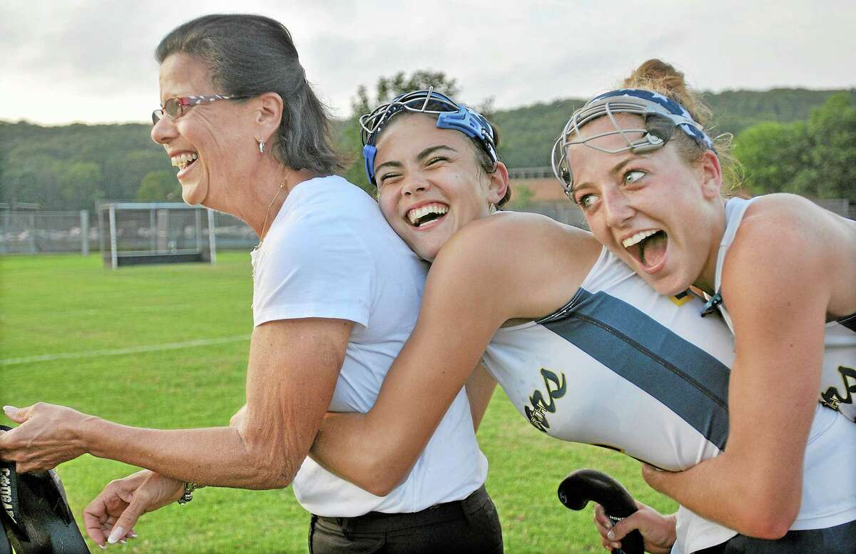 Haddam-Killingworth captains Kolby Burger and Allison Sheahan embrace head coach Patsy Kamercia following her 400th career win. H-K defeated Canton 4-2. Catherine Avalone - The Middletown Press