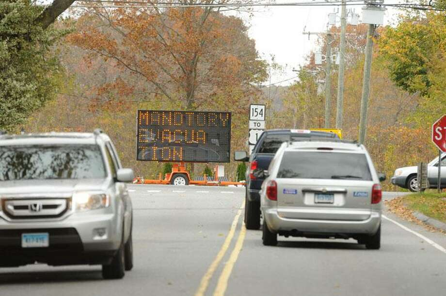"A sign reads ""mandatory evacuation"" at the intersection of Great Hammock Road and Old Boston Post Road in Old Saybrook Sunday. Mara Lavitt/New Haven Register"
