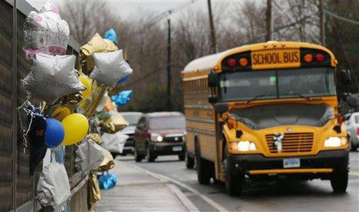 A school bus rolls toward a memorial in Newtown Dec. 18 for victims of the Sandy Hook Elementary School shooting. Nearly three weeks after the shooting rampage, classes are starting Thursday for the Sandy Hook students at a repurposed school in the neighboring town of Monroe, where the students' desks have been taken along with backpacks and other belongings that were left behind in the chaos following the shooting on Dec. 14. Associated Press file photo