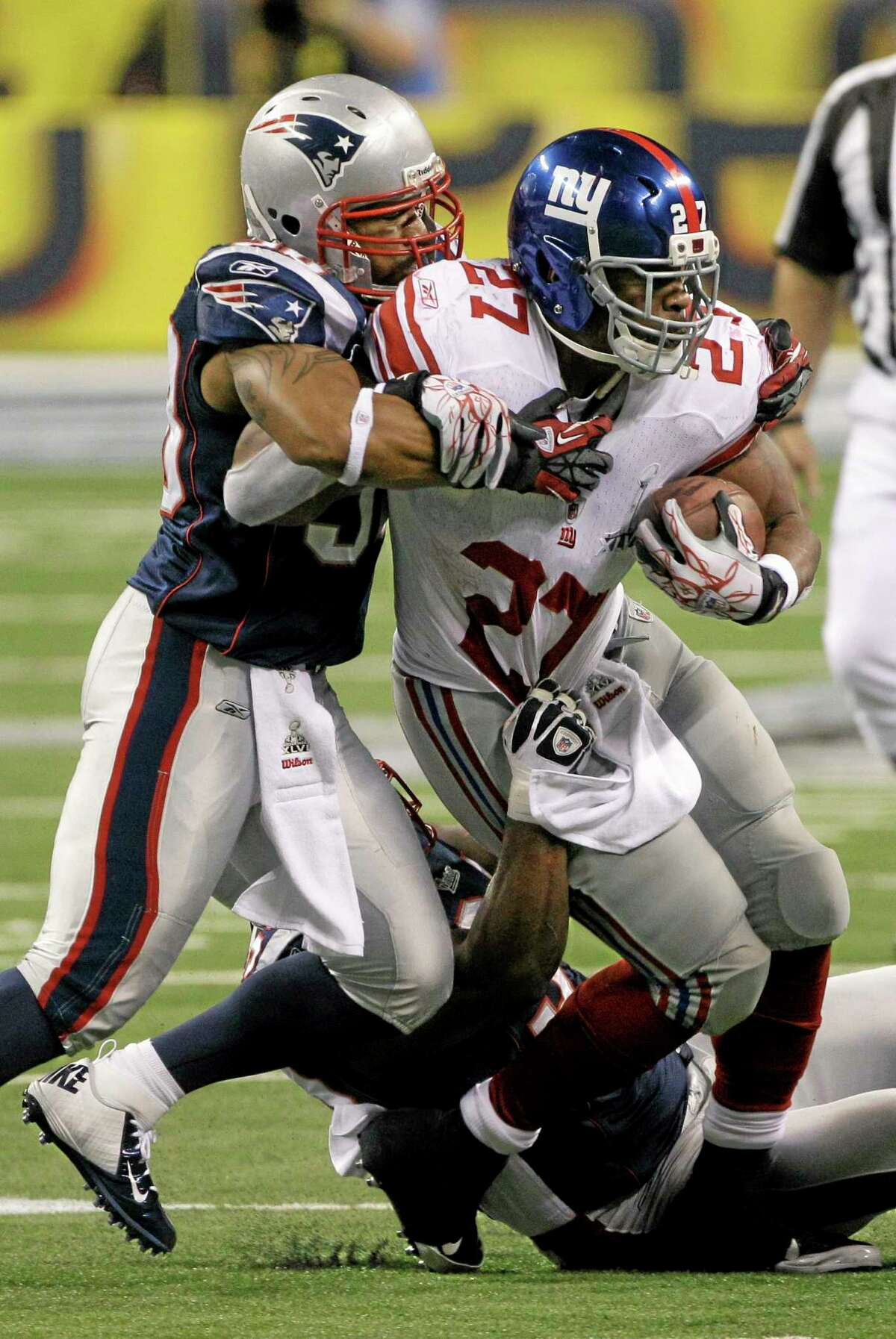 DAVID DUPREY — THE ASSOCIATED PRESS FILE PHOTO In this Feb. 5, 2012, file photo, New England Patriots linebacker Tracy White and defensive end Shaun Ellis tackle New York Giants running back Brandon Jacobs during the first half of Super Bowl XLVI in Indianapolis. Jacobs, who was a part of two Super Bowl-winning teams, signed with the Giants on Tuesday.