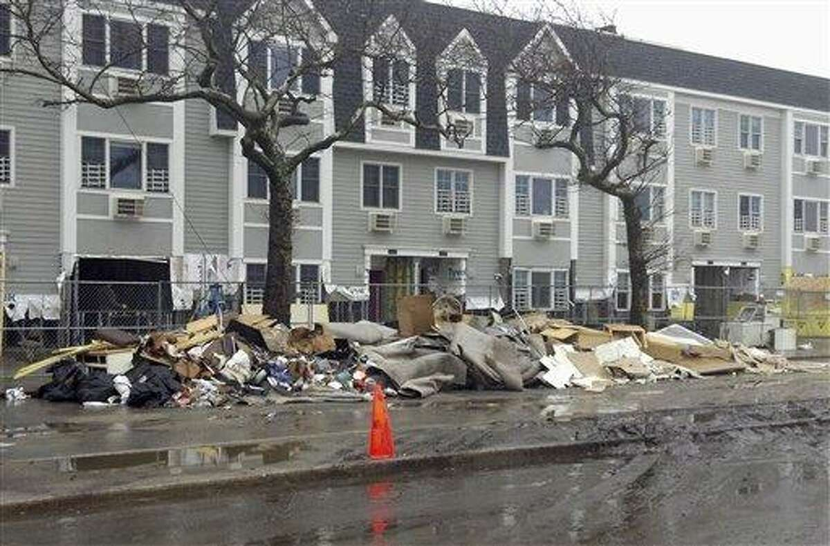 Piles of trash rest against a fence Dec. 10 in front of apartments near Beach 94th in the Rockaways section of New York, an area that was hard hit by Superstorm Sandy and still suffers six weeks after the storm. Associated Press file photo