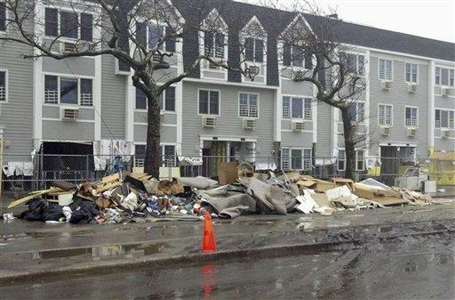 Piles of trash rest against a fence Dec. 10 in front of apartments near Beach 94th in the Rockaways section of New York, an area that was hard hit by Superstorm Sandy and still suffers six weeks after the storm. Associated Press file photo Photo: AP / AP