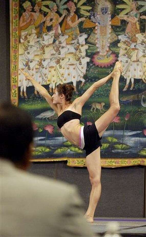 In this 2003 file photo, Jordan Ciambrone of Tempe, Ariz., assumes a yoga position for a panel of judges during the first International Yoga Asana (Posture) Championship, hosted by the Bikram's Yoga College of India, at the Yoga Expo 2003 in the Los Angeles Convention Center. The National Yoga Asana Championship is being put on in New York and run from March 2 through 4, 2012, by an organization that wants to see yoga asana competition become an Olympic sport. Associated Press Photo: AP / AP2003