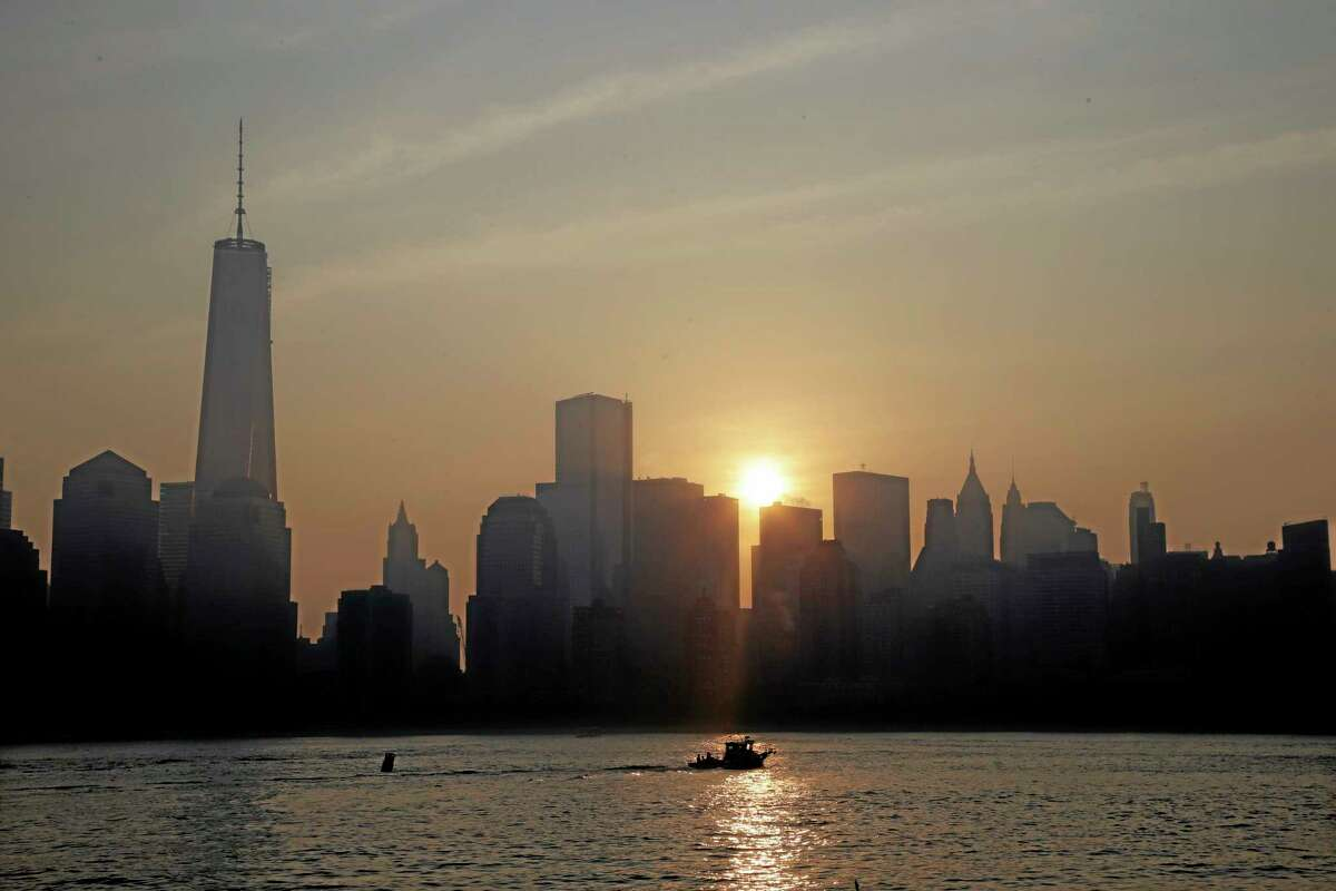 The sun rises in back of One World Trade Center in lower Manhattan, seen from Jersey City, N.J., Wednesday, Sept. 11, 2013. Ceremonies will be held Wednesday to mark the 12th anniversary of the 9/11 terrorist attacks. (AP Photo/Mel Evans)