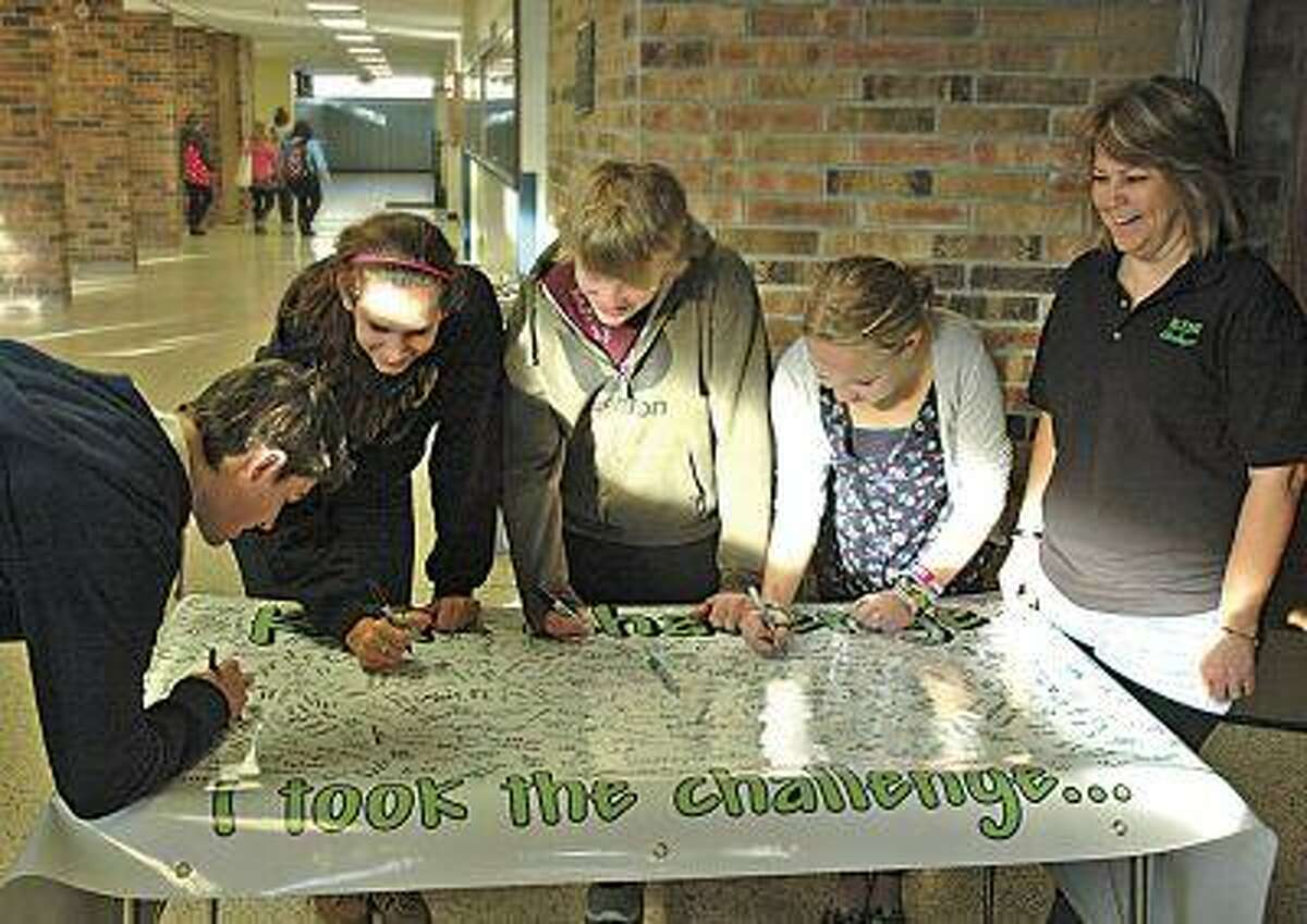 """FILE - This Nov. 3, 2011 file photo shows, from left, Brock Raffaele of Cadillac, Mich. and Sault High students Lauren Gee, Conner Langendorf, and Emma Harrington, taking the KDR Challenge and sign the banner as speaker Bonnie Raffaele, right, watches in Sault Ste. Marie, Mich.. Seventeen-year-old Kelsey Raffaele's last words were over a cell phone to a friend: """"I'm going to crash!"""" The car she was driving had clipped a snow bank and spun into oncoming traffic, where it was t-boned by an SUV. She died at a hospital without regaining consciousness. Police chalked the accident up to mistakes made by a novice driver, unaware that she had been on the phone at the time.(AP Photo/The Evening News, Mike McKee)"""