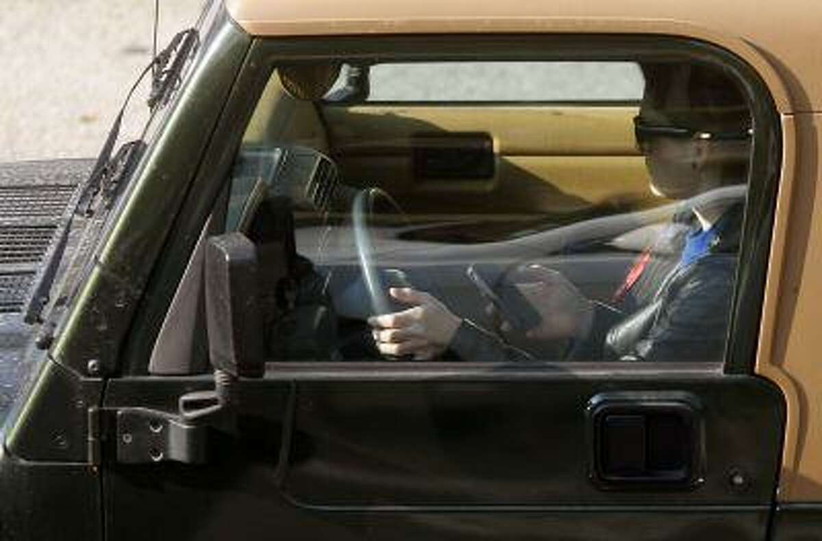 FILE- In this Wednesday, Dec. 14, 2011, file photo, a driver uses an iPhone while driving Wednesday, in Los Angeles. Traffic safety regulators are asking automakers to put stronger limits on how long drivers can use in-car touch screens in an effort to curb distracted driving. The voluntary guidelines unveiled Tuesday April 23, 2013, would restrict the amount of time it takes to perform a single function on the car's audio/visual systems to two seconds. (AP Photo/Damian Dovarganes, File)