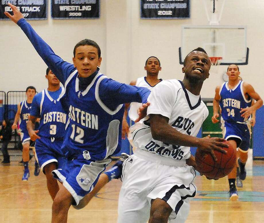 Catherine Avalone/The Middletown PressMiddletown's Jha'kur West drives to the hoop during a fast break as Bristol Eastern's George Taylor defends Monday night in Middletown. The Blue Dragons defeated Bristol Eastern 70-46.