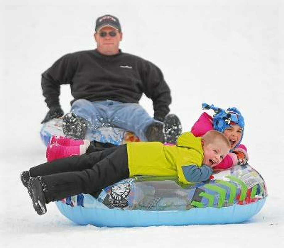 Jason Brody, 40, of East Hampton his 6 year old son, Erik Brody and their friend, Lily Bolgroe, 6, of Wethersfield tandem down Foss Hill on a couple of tubes Monday afternoon at Wesleyan University in Middletown. Catherine Avalone/The Middletown Press