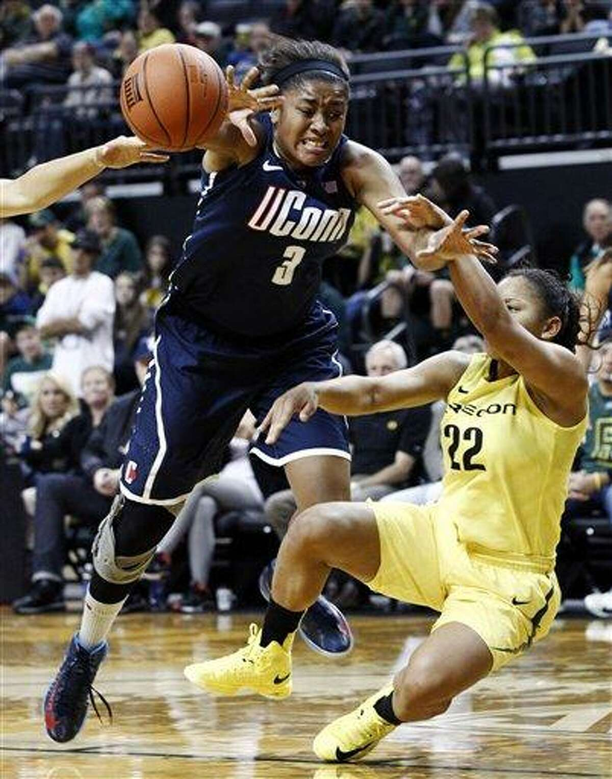 Connecticut forward Morgan Tuck, left, is fouled on her way to the basket by Oregon guard Ariel Thomas during the second half of an NCAA college basketball game in Eugene, Ore., Monday, Dec. 31, 2012. Connecticut won 95-51. (AP Photo/Don Ryan)