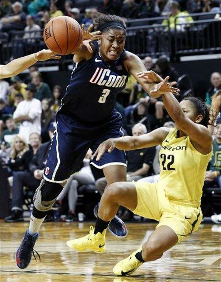 Connecticut forward Morgan Tuck, left, is fouled on her way to the basket by Oregon guard Ariel Thomas during the second half of an NCAA college basketball game in Eugene, Ore., Monday, Dec. 31, 2012. Connecticut won 95-51. (AP Photo/Don Ryan) Photo: AP / AP
