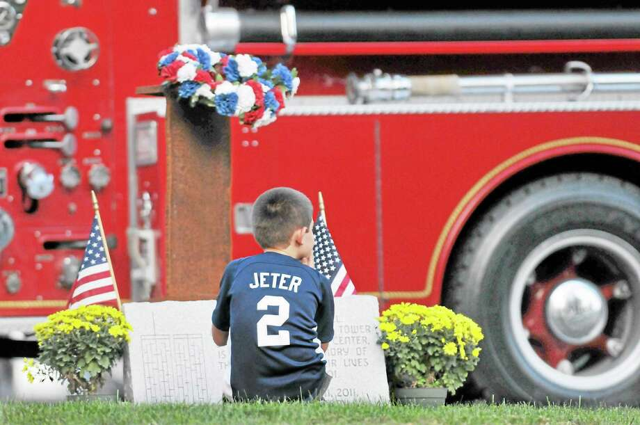 """Although Durham resident Justin Patenaude, 9, stooped down to get a closer look at the beam from World Trade Center following the 9/11 ceremony Wednesday evening at the Middlefield's Volunteer Fire Department, his eyes seem to be focused on the fire truck. Patenaude said, """"I was just looking at the piece of metal, the beam from the North Tower."""" Catherine Avalone — The Middletown Press Photo: Journal Register Co. / TheMiddletownPress"""
