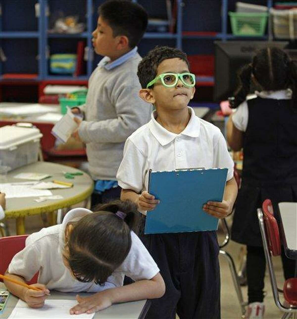 Gabriel Feliciano scans the room for clues while working on a worksheet in a kindergarten class at the Diloreto Magnet School in New Britain Wednesday. As Connecticut lawmakers consider sweeping reforms intended to close the achievement gap between wealthy and poor school districts, another gap is growing: The disparity between communities that offer full-day kindergarten and those that don't. Associated Press