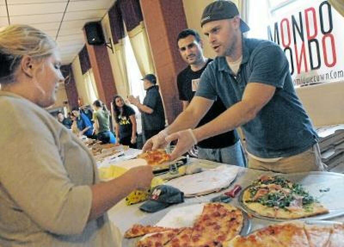 Catherine Avalone/The Middletown Press Manager of Mondo's Pizza Keith Vibert, at right and head chef Dave Noad serves up a slice of their winning pizza to Jessica Rose, of Northford at the Second Annual Middletown Pizza War held at the Sons of Italy on Court Street in Middletown Wednesday evening. Carmine's of Durham placed second and DaVinci Pizza placed third. The event is sponsored by Feed the People Charity and proceeds will benefit St. Vincent dePaul Middletown.