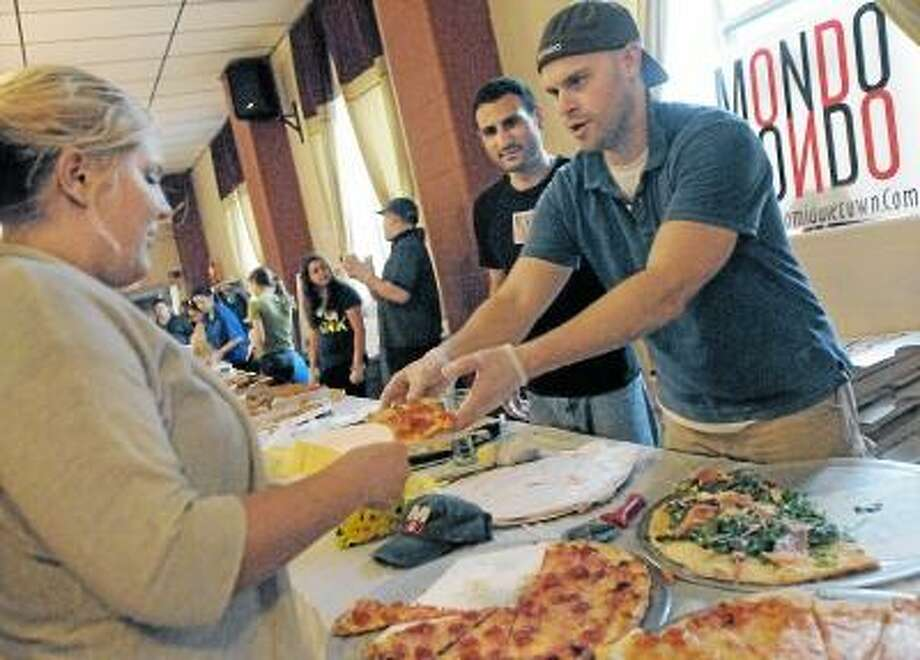 Catherine Avalone/The Middletown Press Manager of Mondo's Pizza Keith Vibert, at right and head chef Dave Noad serves up a slice of their winning pizza to Jessica Rose, of Northford at the Second Annual Middletown Pizza War held at the Sons of Italy on Court Street in Middletown Wednesday evening. Carmine's of Durham placed second and DaVinci Pizza placed third. The event is sponsored by Feed the People Charity and proceeds will benefit St. Vincent dePaul Middletown. / TheMiddletownPress