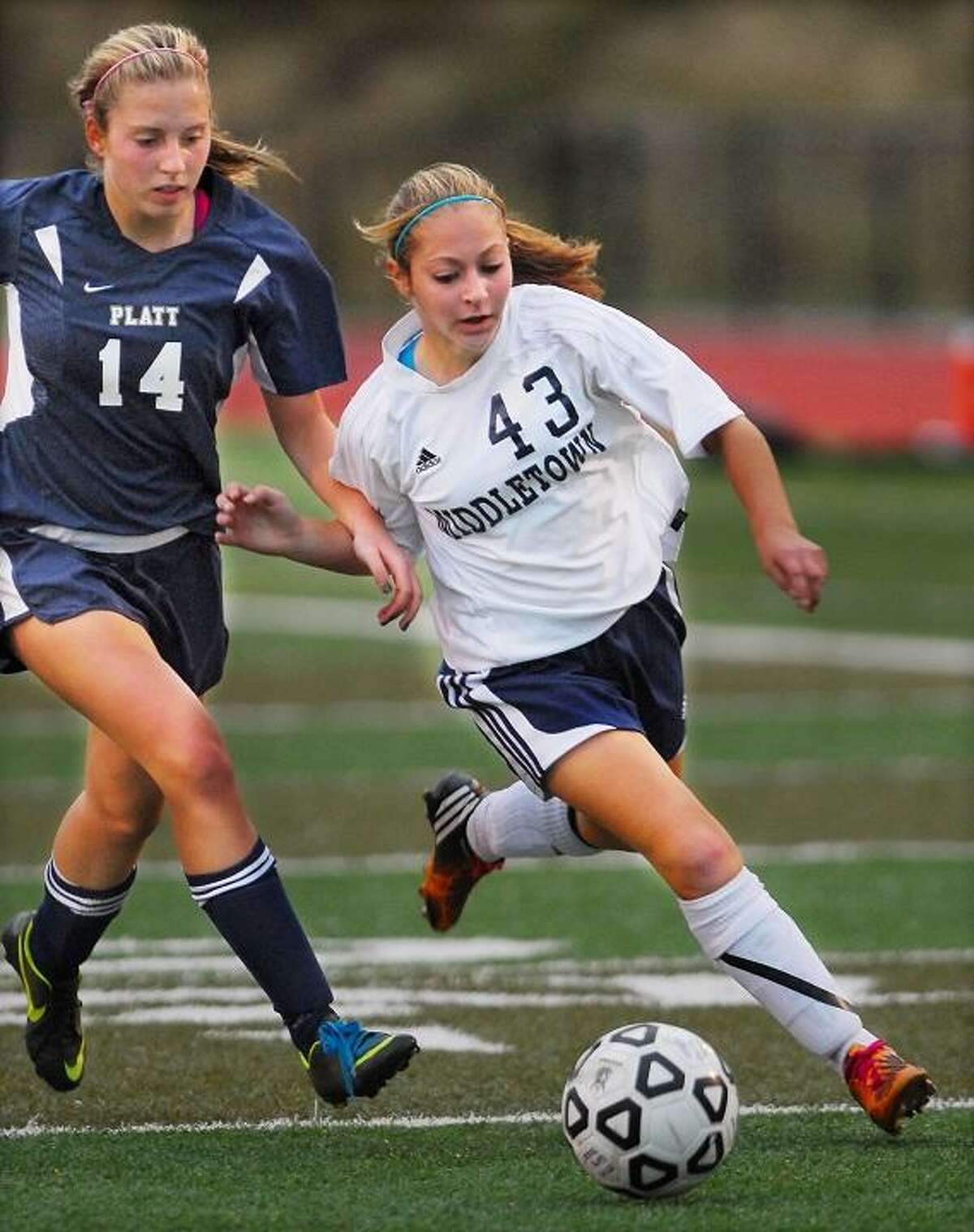 Catherine Avalone/The Middletown Press Middletown forward Kellie Gambell manuevers the ball around Platt junior Jessica Kubeck during a match Friday afternoon. The Blue Dragons defeated Platt 2-1 in overtime and remains undefeated 14-0-1.